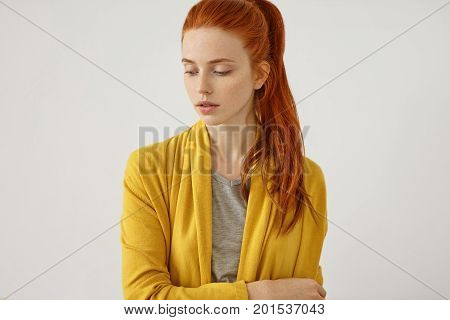 Studio shot of serious red-haired female with freckled skin with no make-up wearing yellow cape standing crossed hands over white background. Beautiful woman with reddish ponytail looking down poster