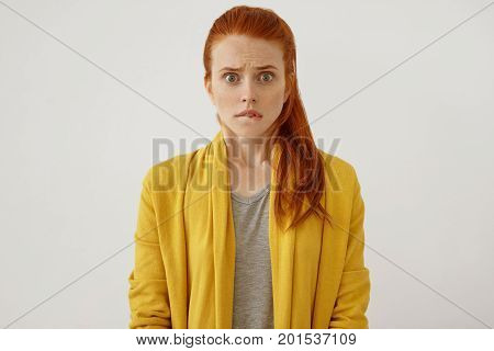 Scared Red-haired Woman With Pony Tail, Stairing At Camera, Curving Her Lips Being Shocked To Realiz