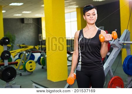 Bodybuilding, gym, people and sport concept - Strong fit girl exercising with dumbbells. Muscular woman lifting weights.