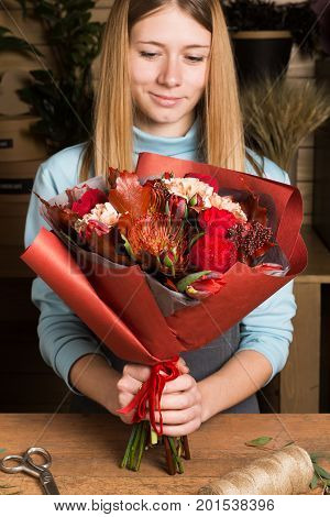 Beautiful florist holding colorful fall bouquet. Smiling woman at flower shop. Floristic design and delivery concept