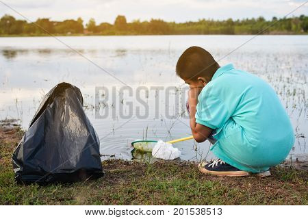 Boy hand in yellow gloves picking up empty of bottle plastic volunteer concept