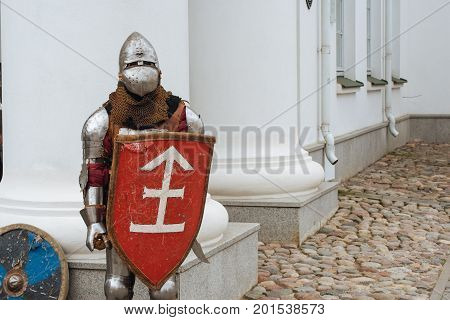 Minsk, Belarus - Aug 26, 2017: A man in knightly armor with a red wooden shield standing by the historic Minsk city hall and some other shield is leaning against the wall