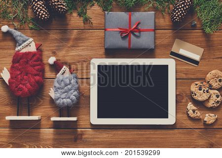 Christmas online shopping background. Tablet screen with copy space top view on wood, credit card, xmas toys and presents. Electronic devices, internet commerce on winter holidays concept