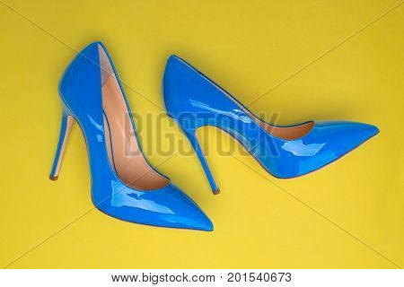 A pair of blue lacquered shoes on a yellow background