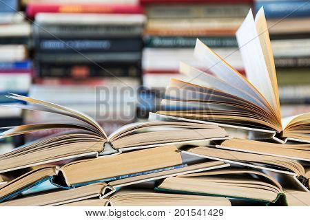 A stack of books with colorful covers. The library or bookstore. Books or textbooks. Education and reading. Open book in the foreground. poster