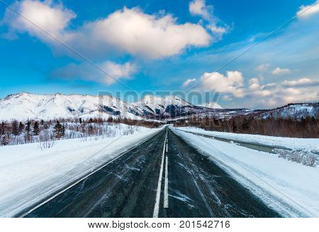 Empty snow covered asphalt dark road with white road marking along mountains and hills and blue sky with clouds. Russia. Island Sakhalin