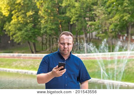 Man in blue shirt uses his smart phone on nature background