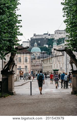 Salzburg Austria - August 6 2017: Scenic cityscape of Salzburg with tourists against castle. The Old Town of Salzburg is internationally renowned for its baroque architecture and was listed as a UNESCO World Heritage Site.