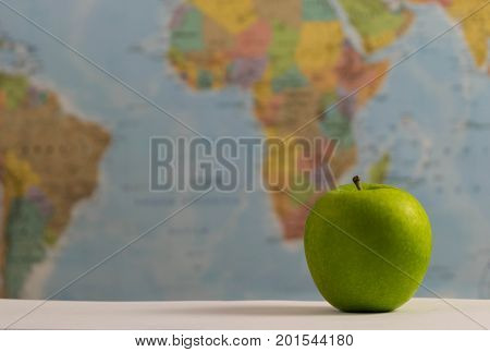 a neat green apple on a world map background