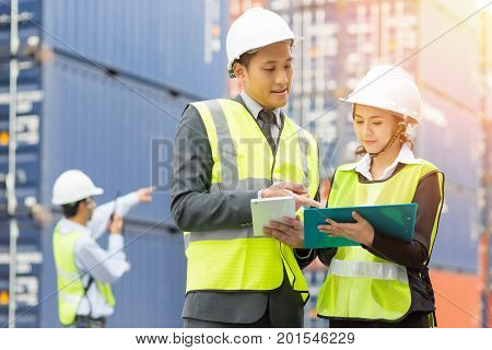 Asian Businessman Asian secretary and Asian Container inspector working in yard with communication device walkie talkie communicate report number checking container.