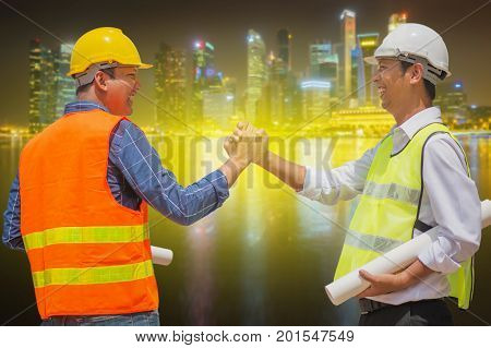 Handsome construction workers in protective helmets and vests are shaking hands while working on city background