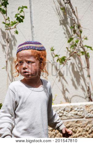 HEBRON ISRAEL - APRIL 12 2009: Orthodox redhead jewish boy walk in jewish quarter. Hebron. Israel