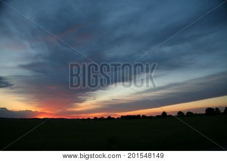 Natural Sunset Sunrise Over Field Or Meadow. Bright Dramatic Sky And Dark Ground. Countryside Landscape Under Scenic Colorful Sky At Sunset Dawn Sunrise. Sun Over Skyline, Horizon. Warm Colours.