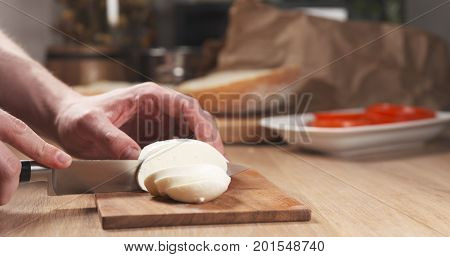 young man hands slicing mozzarella cheese, wide photo