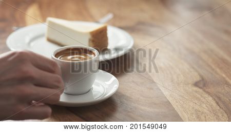 man hand eating cheesecake and drink coffee, wide photo