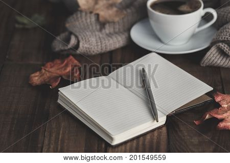 Notebook with pen hot coffee cappucino blanket and autumn leaves on old wooden background. Vintage tonning. Autumn concept