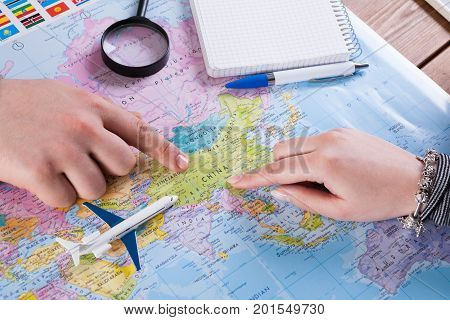 Couple planning airplane trip to China, point on map, taking notes in blank notebook, copy space