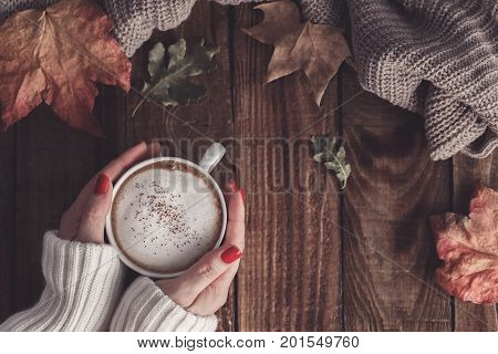 Female hands holding hot coffee cappucino blanket and autumn leaves on old wooden background. Vintage tonning. autumn relax concept