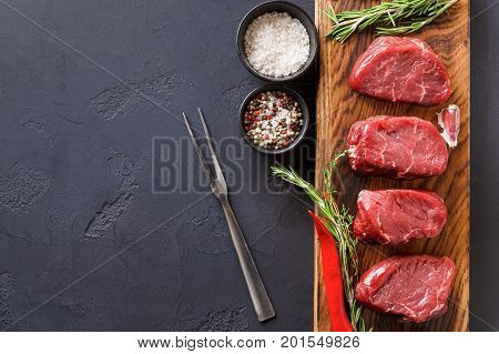 Raw filet mignon steaks with herbs and spices. Ingredients for restaurant dish. Fresh meat, salt, rosemary, garlic and chilli on wooden board, meat fork at black background with copy space, top view