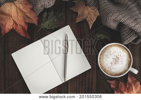 Notebook with pen hot coffee cappucino blanket and autumn leaves on old wooden background. Vintage tonning. Autumn relax concept