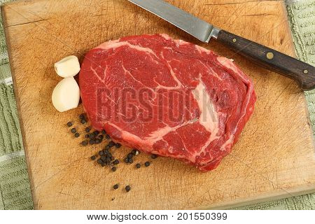 slice of uncooked ribeye steak on a wooden cutting board