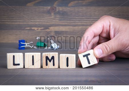Limit from wooden letters on wooden background.