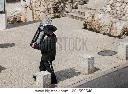 JERUSALEM, ISRAEL - FEBRUARY 21, 2009:  Undefined orthodox jewish man carrying ancient scroll of Torah (first five books (Pentateuch) of the Tanakh)