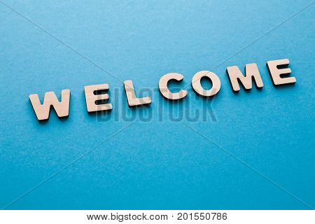 Word Welcome on blue background. Greeting, hospitality, politeness concept