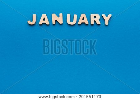 Word January made of wooden letters on blue background.Month planning, timetable concept