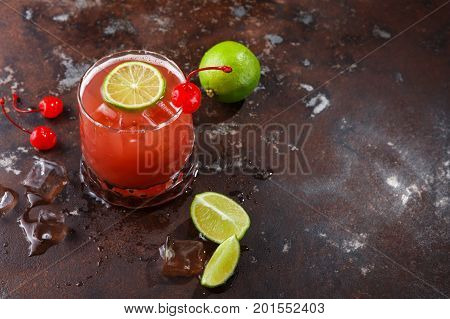 Red cocktail on brown background. Refreshing alcohol drink with tequila, citrus juice, lime and maraschino cherry on dark marbled table with meltig ice and dices of refined sugar, copy space