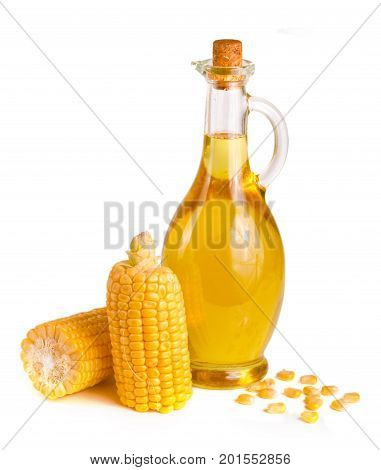 Corn oil in decanter, fresh corn cobs and grains isolated on white background.