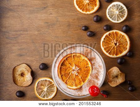 Dry orange, lemon, apple sliceces, chocolate sweets and coffee punch on wooden board. Candied citrus citrons closeup with copy space. Confectionery, bar or christmas background concept