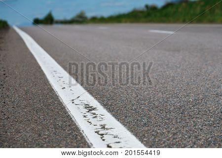 Closeup of asphalt highway with road markings. Asphalt texture and background with white solid line. Transportation and safety driving concept