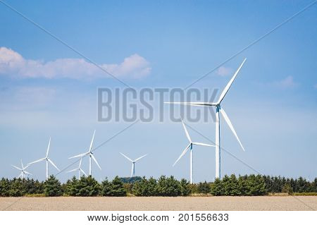 Many wind turbines spinning against a blue sky in southern Ontario Canada