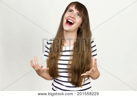 Portrait of a pretty woman screaming spreads her hands on the sides and crooked fingers and standing over gray background