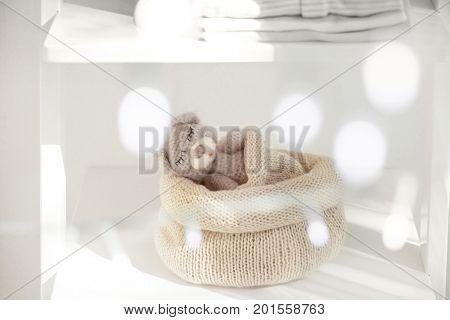 Cute handmade toy bear sleeping in knitted bag on shelf