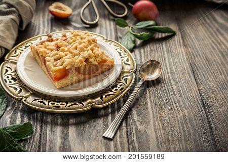 Plum crumb cake pie cut into squares. Healthy autumn food concept. Toned photo. Copy space.