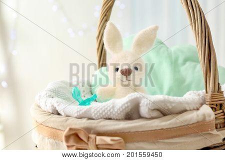Cute knitted toy bunny in wicker basket