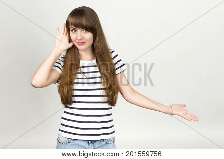 Portrait of a pretty woman overhears and tries to listen over gray background