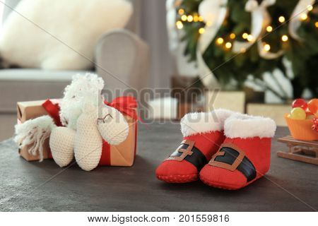 Cute booties for baby and toy on table in decorated room for Christmas