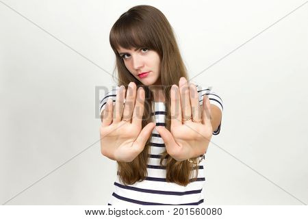 Portrait of a pretty woman standing over gray background showing stop with one hand and looking at camera with disgust and closes her nose