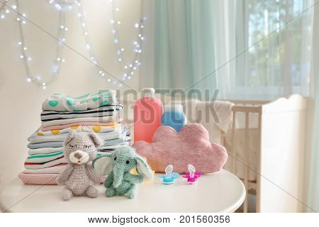 Cute knitted toys, baby clothes and accessories on table in room