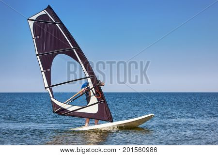 Windsurfer man in wetsuit windsurfing on board with colorful sail in calm sea or ocean on sunny day on blue sky background. Recreational water sports during idyllic summer vacation