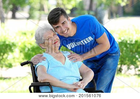 Happy senior woman on wheelchair with young male volunteer outdoors