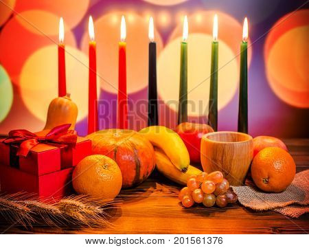 Kwanzaa Festive Concept With Seven Candles Red, Black And Green, Gift Box, Pumpkin, Bowl And Fruit O