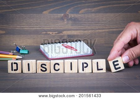 Disciple from wooden letters on dark texture background