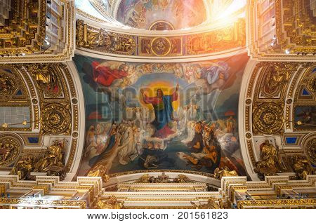 ST PETERSBURG RUSSIA - AUGUST 15 2017. Ceiling decorated with sculptures and Bible paintings in the interior of the St Isaac Cathedral in St Petersburg Russia. St Petersburg Russia landmark interior view