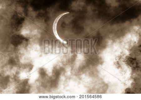 the Partial Solar Eclipse shining Through Clouds