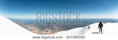 Panorama of the North Caucasus with the participation of tourists descending from the top of Mount Elbrus. View of the summer northern caucasus from the snow-capped summit of Elbrus