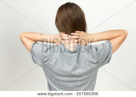 Portrait of a pretty woman holding her neck in pain and discomfort standing over gray background